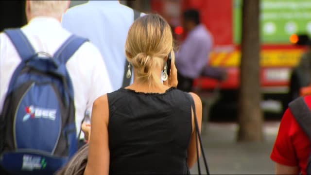 vidéos et rushes de various shots people use smart phones in city streets woman walking along in hyde park holding mobile phone and glances at it / city street anon... - piétons