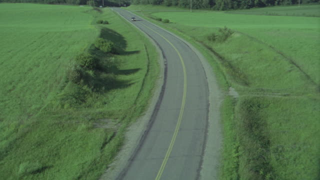 stockvideo's en b-roll-footage met aerial of lush green countryside full of fields, trees, jeep suv driving up winding road, with a clear view to the horizon. beauty shots. - manitoba