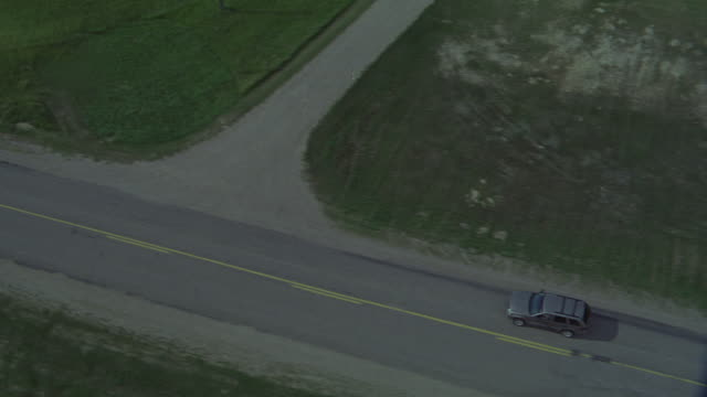 stockvideo's en b-roll-footage met aerial tracking shot of jeep or suv driving up highway between fields with silos. countrysides. telephone poles. some cars traveling in opposite direction. - manitoba