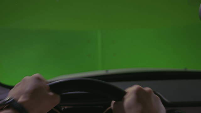 vídeos y material grabado en eventos de stock de hand held drivers pov shot of a man's hands on the steering wheel of a car or sedan.  his hands tightly move back and forth as if he's driving fast.  special effect green screen. - interior del coche
