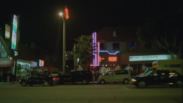 MEDIUM ANGLE OF CARS DRIVING ON SUNSET BLVD.  STREET LINED WITH PALM TREES, PARKED CARS, NEON SIGNS AND STREET LIGHTS. ROXY BAR AND MUSIC CLUB IN BG. WEST HOLLYWOOD. SUNSET STRIP.