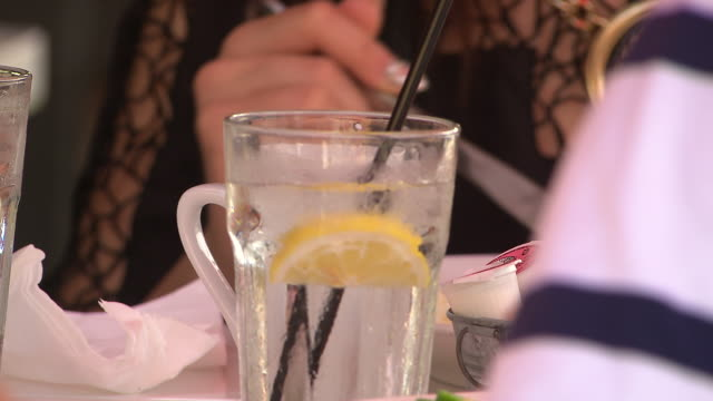 CLOSE ANGLE OF PEOPLE'S HANDS EATING BREAKFAST OR BRUNCH AT RESTAURANT. WATER WITH LEMON.