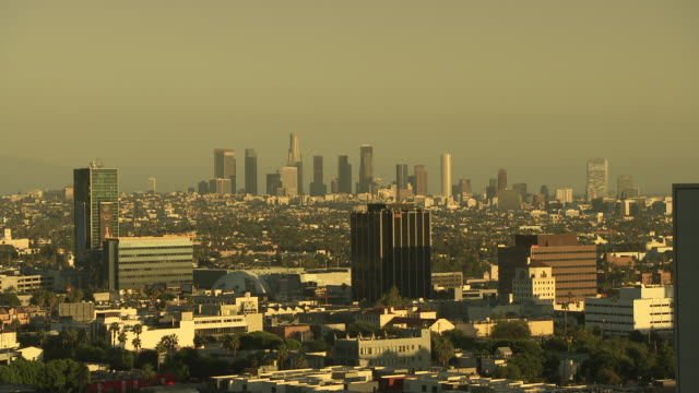 WIDE ANGLE OF SUN SETTING OVER LOS ANGELES CITY SKYLINE.