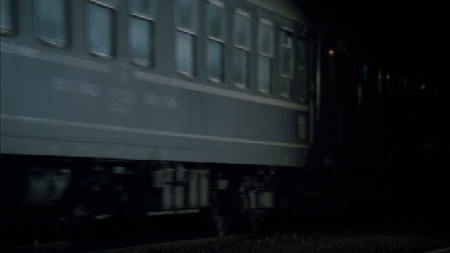 CLOSE ANGLE OF TRAIN MOVING BY RIGHT TO LEFT ON TRAIN RACKS. RAILROAD TRACKS. COULD BE EASTERN EUROPE. CLOSE UP OF TRAIN WHEELS.