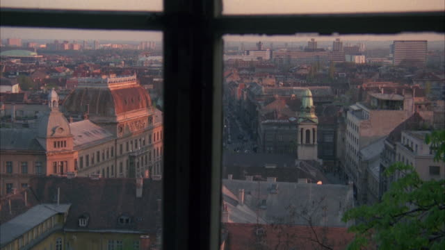 high angle down from window of city skyline and buildings below. sign on building reads medimurska. bricks buildings. could be apartment buildings. could pass for any eastern europe city. tower with with green dome and steeple in fg. sunset. - steeple stock videos & royalty-free footage