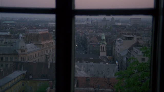 high angle down from window of city skyline and buildings below. sign on building reads medimurska. bricks buildings. could be apartment buildings. could pass for any eastern europe city. tower with with green dome and steeple in fg. dusk. - steeple stock videos & royalty-free footage