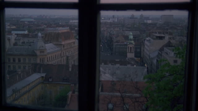 HIGH ANGLE DOWN FROM WINDOW OF CITY SKYLINE AND BUILDINGS BELOW. SIGN ON BUILDING READS MEDIMURSKA. BRICKS BUILDINGS. COULD BE APARTMENT BUILDINGS. COULD PASS FOR ANY EASTERN EUROPE CITY. TOWER WITH WITH GREEN DOME AND STEEPLE IN FG. DUSK.