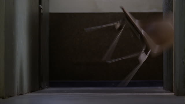 vidéos et rushes de medium angle of chair being thrown out into hallway. could be office building. chair could be thrown in fit of rage. - chaise
