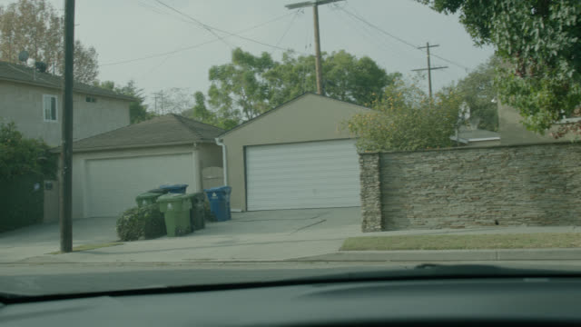 medium angle straight forward driving pov from car of suburban neighborhood. - telegraph pole stock videos and b-roll footage