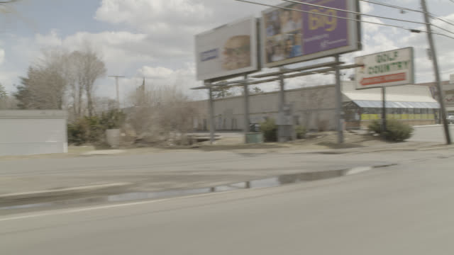 vídeos de stock, filmes e b-roll de process plate 3/4 back right of cars driving on small town road.  could be small town freeway or highway. - localidade pequena