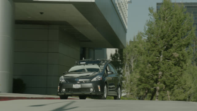 vidéos et rushes de medium angle of cars driving on city street in century city. office buildings visible. could be exiting parking garage. - président