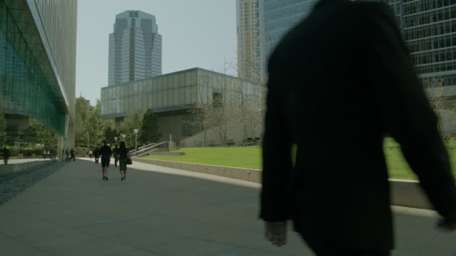 wide angle of walkway or sidewalk in century city. park and businesspeople visible. fox plaza building visible. - beverly hills stock-videos und b-roll-filmmaterial