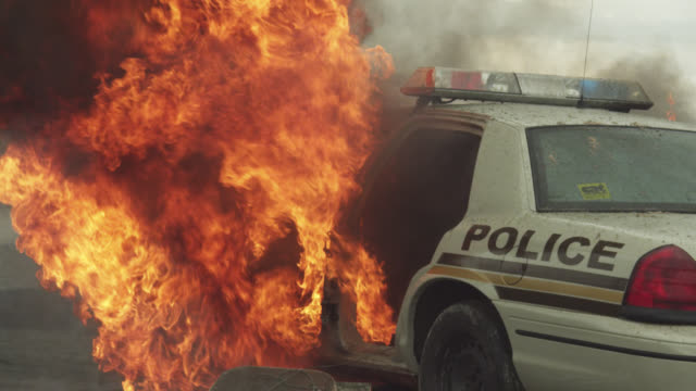 medium angle of police car on fire by lake or ocean. fires, flames, and smoke visible. could be explosion. - police car stock videos & royalty-free footage