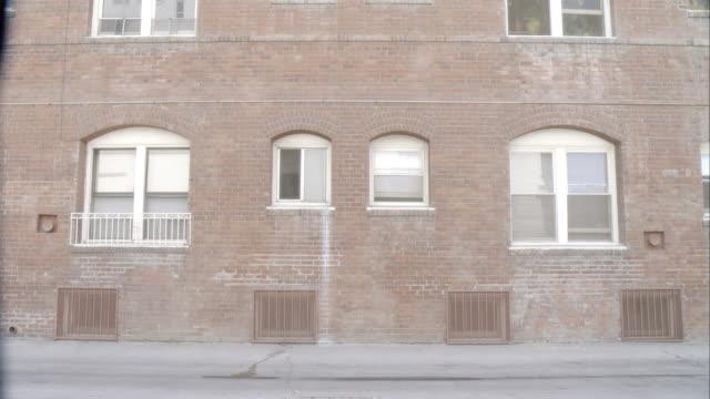 MEDIUM ANGLE OF BRICK WALL OF MULTI-STORY APARTMENT BUILDING.