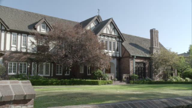 zoom in on two story upper class tudor house or mansion. - 邸宅点の映像素材/bロール
