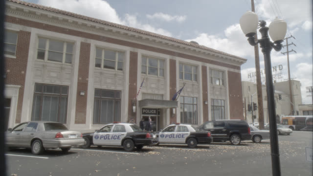 WIDE ANGLE OF POLICE STATION WITH POLICE CARS PARKED IN FRONT. BRICK BUILDING. ACTUALLY IN LOS ANGELES.