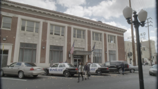 wide angle of police station with police cars parked in front. brick building. actually in los angeles. - 警察点の映像素材/bロール