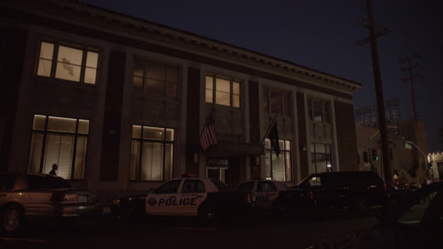 medium angle of police station with police cars parked in front. brick building. actually in los angeles. - police station stock videos & royalty-free footage