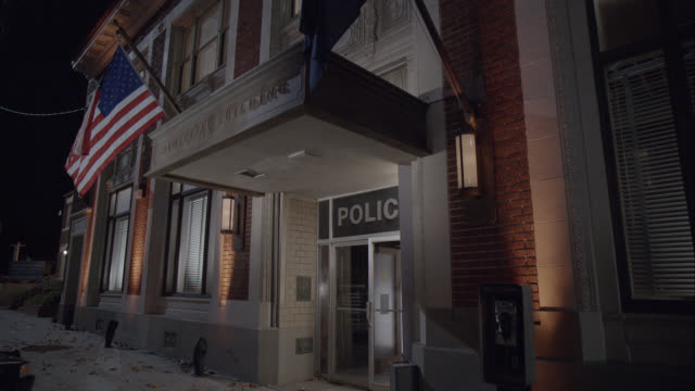 MEDIUM ANGLE OF ENTRANCE OF POLICE STATION. BRICK BUILDING. SIGN FOR FBI AGENT. ACTUALLY IN LOS ANGELES.