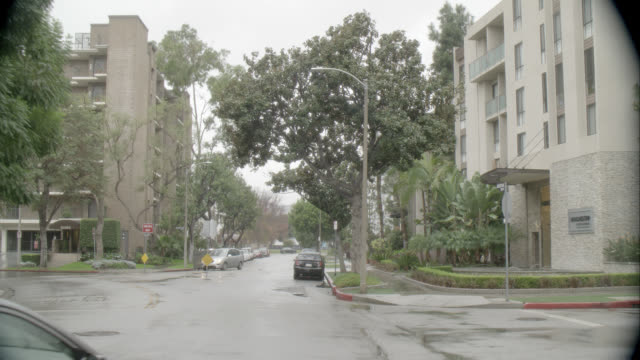 vídeos y material grabado en eventos de stock de pan left to right of intersection in residential area with multi-story middle class apartment buildings. westwood. raining. - westwood neighborhood los angeles