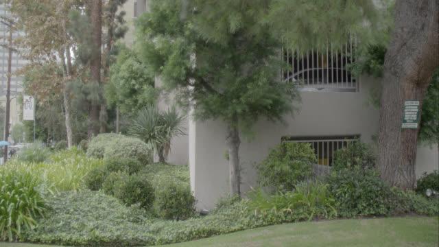 vídeos de stock e filmes b-roll de medium angle of multi-story middle class apartment building. westwood. raining. - westwood