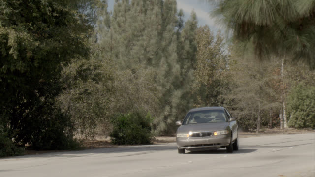 MEDIUM ANGLE OF CAR DRIVING, SWERVING ON ROAD. COULD BE LOSING CONTROL OR ACCIDENT. TREES IN FOREST. CAR STUNT.