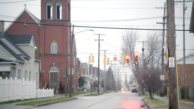 medium angle of residential area street. lower to middle class houses. church. neighborhoods. - cleveland ohio stock videos and b-roll footage