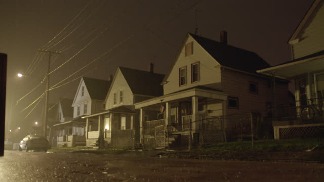 medium angle of two story lower class houses. raining. police car with lights and sirens drives by. - cleveland ohio stock videos and b-roll footage