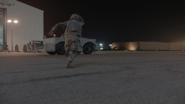 PAN RIGHT TO LEFT OF SOLDIERS RUNNING ON MILITARY BASE. HANGAR AND MILITARY JEEP IN FG. COULD BE ATTACK OR INVASION.