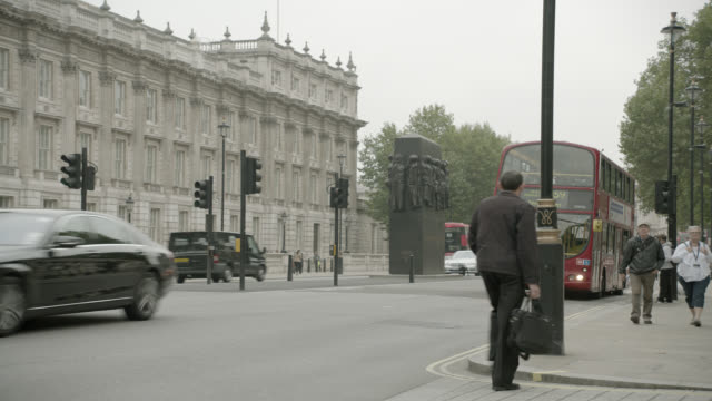 pan right to left of double decker bus driving on city street near entrance to 10 downing street and government buildings. whitehall sw1. pedestrians, tourists, and cars visible. women of world war ii monumnet or memorial visible. - 10 downing street stock videos and b-roll footage