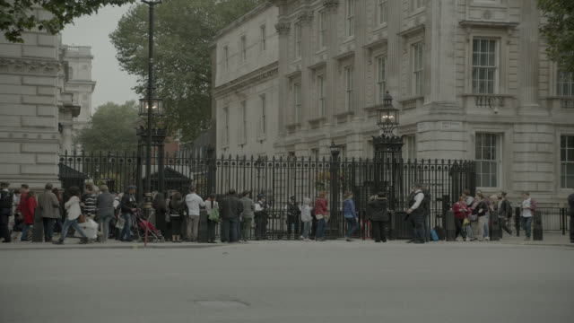 pan right to left of double decker bus driving on city street near entrance to 10 downing street and government buildings. whitehall sw1. pedestrians, tourists, and cars visible. women of world war ii monumnet or memorial visible. - downing street stock videos & royalty-free footage