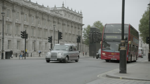 pan right to left of double decker bus driving city street near entrance to 10 downing street and government buildings. whitehall sw1. pedestrians and tourists visible. women of world war ii monumnet or memorial visible. - world politics stock videos & royalty-free footage