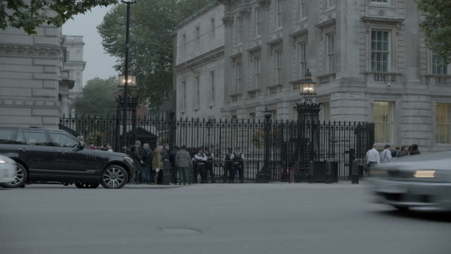 pan right to left of taxi driving city street near entrance to 10 downing street and government buildings. whitehall sw1. pedestrians and tourists visible. women of world war ii monumnet or memorial visible. - world politics stock videos & royalty-free footage