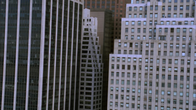 aerial of high rises and skyscrapers in financial district of midtown manhattan. focus on the 120 wall street building in new york city. - financial building stock videos and b-roll footage