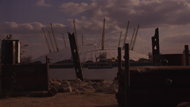 medium angle of millennium dome on river thames. yellow support towers with cords visible. exhibitions. - the o2 england stock videos & royalty-free footage