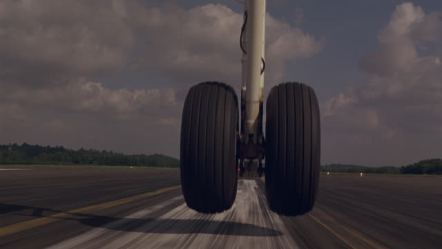 vídeos de stock, filmes e b-roll de close angle moving pov shows landing gear, airplane tires touching down on runway and taking off from tarmac. could be used for commercial airliners or private jets. planes. series. - aterrissando