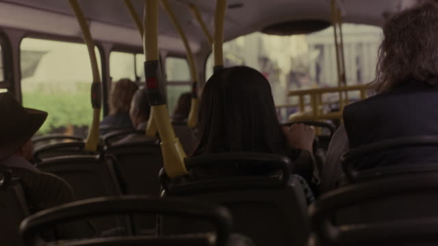 HAND HELD SHOT FROM INSIDE TOP LEVEL OF DOUBLE DECKER BUS DRIVING THROUGH LONDON. SEVERAL PASSENGERS SITTING IN SEATS. WOMAN AND MAN TALK TO EACH OTHER AND LOOK TOWARDS CAMERA AT BACK OF BUS, AS IF TALKING ABOUT SOMEONE IN THE BACK. TOUR BUSES, BUILDINGS