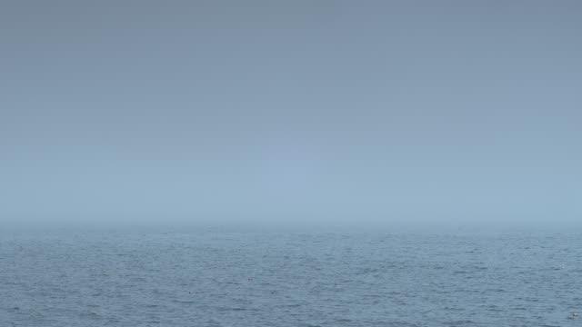 MEDIUM ANGLE OF MIST OR FOG OVER OCEAN OR LAKE.