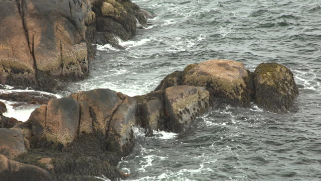 MEDIUM ANGLE OF WAVES HITTING ROCKS.