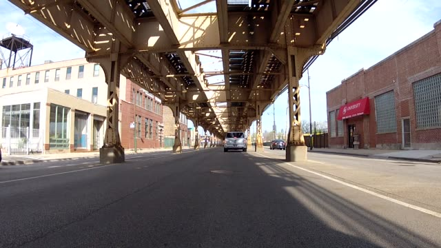 vídeos de stock, filmes e b-roll de process plate driving straight forward pov on city street with other cars under elevated tracks. could be part of car chase. - stationary process plate