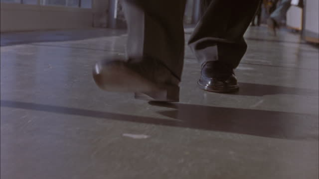 MEDIUM ANGLE MAN'S FEET WALKING ON STONE OR CONCRETE PAVEMENT OR FLOOR. SEE MAN WEARING BLACK DRESS SHOES AND BLACK SLACKS OR PANTS. CAMERA PULLS BACK AS MAN WALKS TOWARDS CAMERA.