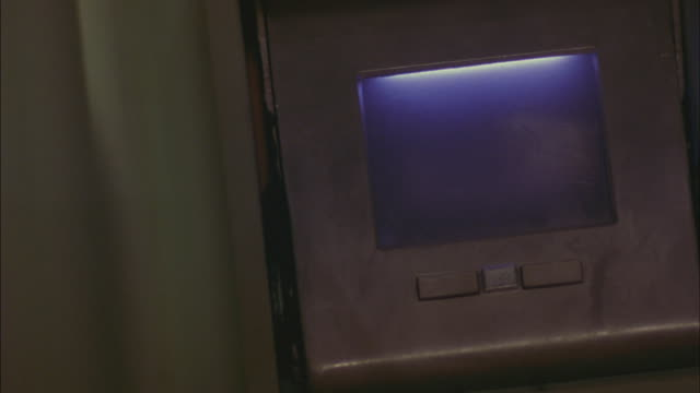MEDIUM ANGLE OF FUTURISTIC FINGERPRINTING SCANNER. SEE GREEN NEON LIGHT, OR SCAN LIGHT. LASERS. HANDS.