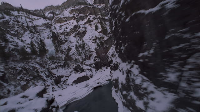vídeos de stock e filmes b-roll de aerial of forward window pov from helicopter or airplane flying through mountain gorge in winter. see partially frozen river with ice and open water. see exposed rocks through snow and coniferous evergreen trees. could be canyon, ravine, or valley. - vale