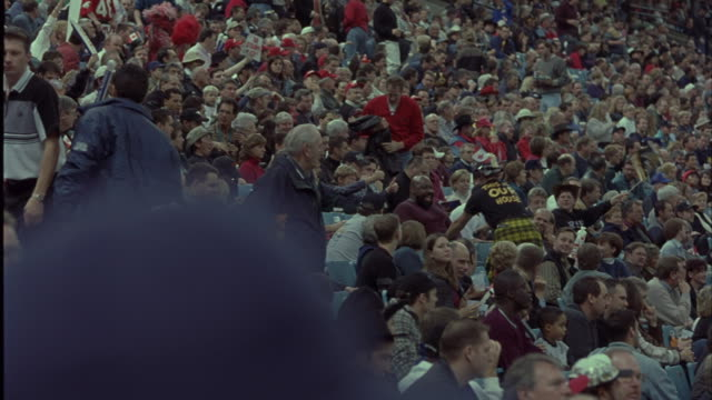 wide angle of crowd in stadium seats. see people walking in aisles, standing up, waving flags, cheering, and dancing. could be football, baseball, basketball, or hockey game in sports arena. spectators. - baseballmütze stock-videos und b-roll-filmmaterial