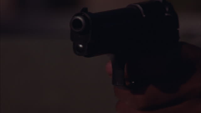 close angle of black pistol or hand gun, could be beretta, firing five shots. see dark skin-toned fingers gripping handgun trigger. - handgun stock videos and b-roll footage