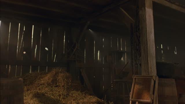 medium angle of barn. see haystack in foreground. see wooden barrels in foreground. - haystack stock videos & royalty-free footage