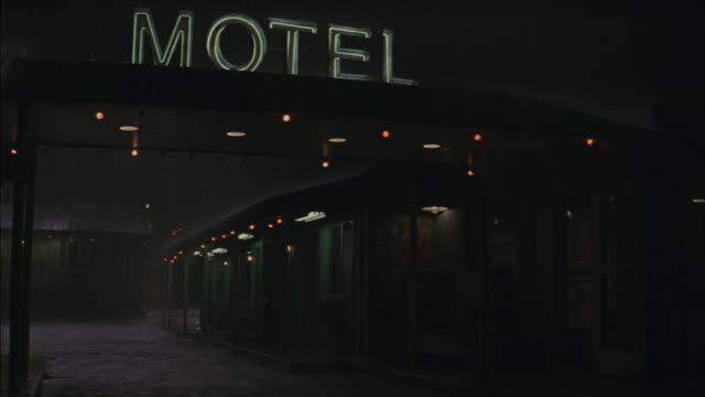 medium angle of entrance to motel. see neon sign that reads motel on top of porte-cochere with dim lights. see doors to rooms of motel in the background. - motel stock videos and b-roll footage