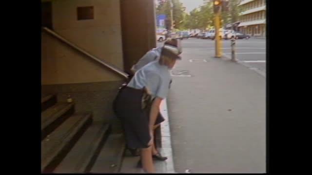 sally young reports on shooting massacre at telecom building in queen street melbourne: two police women crouching in building entrance steps zoom in... - 1987 bildbanksvideor och videomaterial från bakom kulisserna