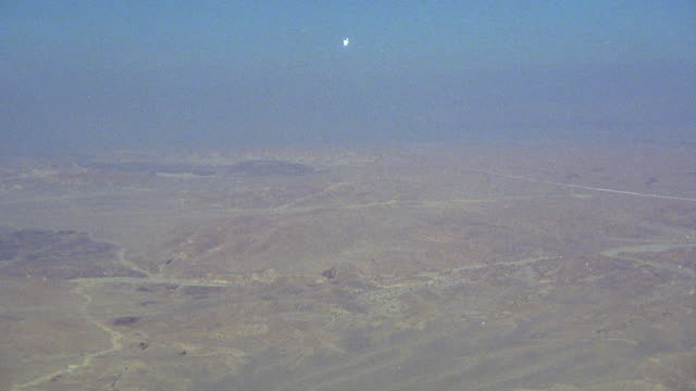AIR-TO-AIR AERIAL TRACKING SHOT OF CAMOUFLAGE MILITARY F-16 FIGHTER JET AIRPLANE PULLING UP FROM DESERT FLOOR. MIDDLE EAST.