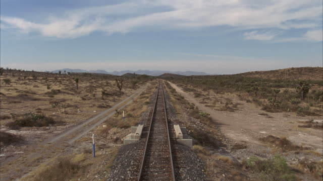 process plate from back of train. see train tracks in foreground. see desert with cactus and bushes. - absence stock videos & royalty-free footage